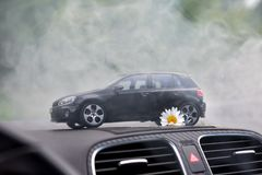 Moscow. Autumn 2018. Black toy car stays in smoke on dashboard of the same real car. Volkswagen golf 6, logo mat vw