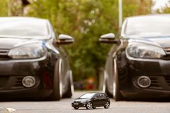 Moscow. Autumn 2018. Two real full size black Volkswagen Golf and a small toy such Golf between them. Family concept. Tuning VW
