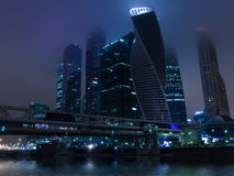 Moscow city night fog. Modern contemporary city architecture: Moscow City commercial center by night in mist and fog illuminated. Includes skyscreper buildings Stock Photo