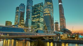 Moscow City skyline sunset time lapse. Moscow International Business Centre skyline at golden hour with Bagration Bridge and Moskva river in foreground stock video footage