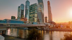 Moscow City skyline sunset time lapse. Moscow International Business Centre skyline at golden hour with Bagration Bridge and Moskva river in foreground stock video