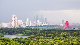 Moscow cityscape in the light mist. Panoramic view of two totally different kinds of urban landscape under the rain. Place of the collision of nature and human Stock Photo