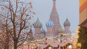 Moscow is decorated for New Year and Christmas holidays. Christmas balls on the branches of trees near the Cathedral of St. Basil the Blessed on Red Square stock footage