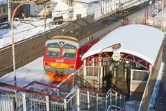 MOSCOW, FEB. 01, 2018: Winter view on red railway passenger train coming to station and stairway to platform through the ticket ba stock photos