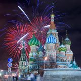 Moscow firework. Saint Basil's Cathedral at the Red Square in Moscow by a winter night with firework as a background. Roof is covered by snow royalty free stock photography