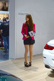 Moscow International Automobile Salon Taffic Women in short black dress and in a crimson jacket. Moscow International Automobile Salon Taffic Visitors to the stock image