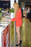 Moscow International Automobile Salon Taffic Young blond women in short red dress near magazines stand. Moscow International Automobile Salon Taffic royalty free stock photo