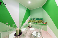 MOSCOW - JULY 2014: Interior of the hookah and anticafe MELLOW-YELLOW. Green room with sofa and glass table Royalty Free Stock Photos