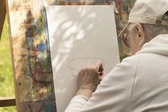 Senior grey-haired man draws with left hand at art studio stock images