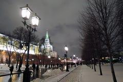 Moscow Kremlin and Alexanders garden at night. Color winter photo. Moscow Kremlin and Alexanders garden at night. Dark blue sky. People walk in Alexangers garden stock photo