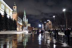 Moscow Kremlin and Alexanders garden at night. Color winter photo. Moscow Kremlin and Alexanders garden at night. Dark blue sky. People walk in Alexangers garden royalty free stock photography