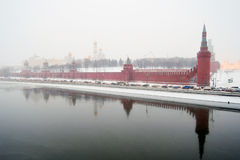 Moscow Kremlin at snowstorm. Old fortress is reflected in grey water. Stock Photo