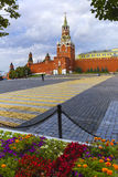 Moscow Kremlin, Spasskaya Tower, Red Square at early morning, framed by leaves and flowers. Spassky Tower of the Moscow Kremlin at dawn royalty free stock images
