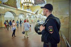 MOSCOW, MAY, 13, 2018: Russian police man in bulletproof vest at metro railway station Komsomolskaya with people in the background. Police securing people and Stock Photos