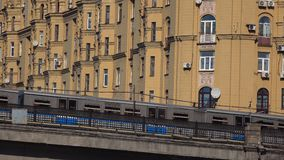 Moscow metro train with city emblem passing bridge against old yellow building. Clip stock video footage