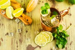 Moscow mule cocktail in copper mug. Moscow mule cocktail with mint, lime and vodka in copper mug. Summer drink on wooden background Royalty Free Stock Photo