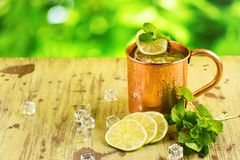 Moscow mule cocktail in copper mug. Moscow mule cocktail with mint, lime and vodka in copper mug. Summer drink on wooden background Stock Photos