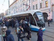 MOSCOW, NOV. 13, 2018: View on modern tramway and a lot of people trying to get in. Morning hard heavy traffic and people in the q. Ueue. City passenger royalty free stock image