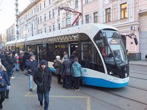 MOSCOW, NOV. 13, 2018: View on modern tramway and a lot of people trying to get in. Morning hard heavy traffic and people in the q. Ueue. City passenger stock image