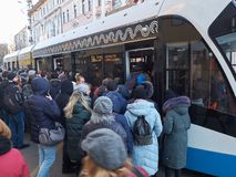 MOSCOW, NOV. 13, 2018: View on modern tramway and a lot of people trying to get in. Morning hard heavy traffic and people in the q. Ueue. City passenger royalty free stock photo