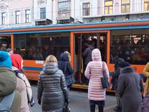 MOSCOW, NOV. 13, 2018: View on modern tramway and a lot of people trying to get in. Morning hard heavy traffic and people in the q. Ueue. City passenger royalty free stock photos