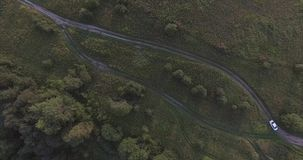 Moscow oblast, Russia. Top view of the long and narrow road, surrounded by green meadows. Riding a white car. stock video