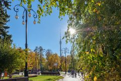 Moscow - October 12, 2018: Beautiful sunny day in Ostankino park. People walk in autumn park. The beam of sun light make their way. Through the foliage of the stock photos