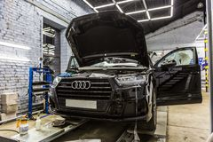 Moscow. October 2018. Decaling of the Audi Q7 with a special protective vinyl film. Germany SUV car is pulling armored film stock image