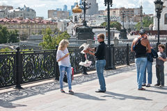 Moscow. On the Patriarshy Bridge. MOSCOW, RUSSIA - July 22.2015: Man-photographer offers to the girl to be photographed with hand pigeons royalty free stock photography