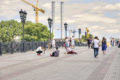 Moscow. On the Patriarshy Bridge. MOSCOW, RUSSIA - July 22.2015: People are photographed sitting in the Patriarshy, Bridge royalty free stock images