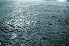 Moscow pavement. Pavement of rectangular blocks at the Red Square in Moscow covered by durty snow and alight by streetlight. Landscape orientation Royalty Free Stock Photo