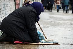 moscow Rússia - Em janeiro de 2018 Mulher desabrigada triste que senta-se nos povos da rua que passam perto Fotos de Stock Royalty Free