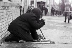 moscow Rússia - Em janeiro de 2018 Mulher desabrigada triste que senta-se nos povos da rua que passam perto Foto preto e branco Fotografia de Stock Royalty Free