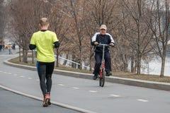 moscow R?ssia 9 de abril de 2019 Um homem em uma bicicleta vai encontrar um homem que cometa uma corrida Lazer dos esportes em Mo imagens de stock
