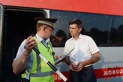 The inspector of the road police patrol checks documents from the driver of the intercity passenger bus. MOSCOW REGION, RUSSIA - AUGUST 3,2017: The inspector of Royalty Free Stock Photo