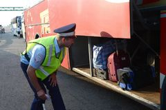 The inspector of the road police patrol checks the luggage compartment of the intercity passenger bus. MOSCOW REGION, RUSSIA - AUGUST 3,2017: The inspector of Royalty Free Stock Image