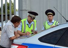 An inspectors of the road police patrol service makes a report on the violation of traffic rules. MOSCOW REGION, RUSSIA - AUGUST 3,2017: An inspectors of the Royalty Free Stock Images