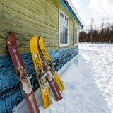 Moscow region, Russia - February 24, 2018: Two pair of old fashioned wooden skis standing near old house on white snow royalty free stock photo