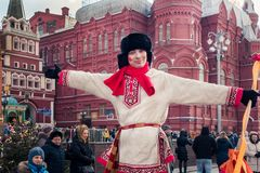 a man in a fur hat and in Russian national costume stands next to the Moscow Kremlin. stock photography
