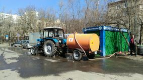 Moscow, RF-2019, March, 17: tractor with tank watering the streets of the city, the green building with the inscription royalty free stock photos