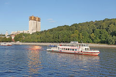 Moscow river with a boat and Russian Science Academy building. Stock Photos