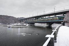 Moscow River. Luzhnetskaya embankment in winter. River cruise ship sails under the Luzhniki bridge. View from the snow-covered embankment to the Vorobyovy Gory Stock Photography