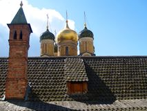 Moscow roof. Wooden roof with chimney and churc onion towers in the background Royalty Free Stock Images