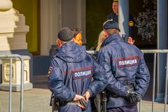 MOSCOW, RUSSIA- APRIL, 24, 2018: Back view of unidentified people wearing police uniform to protect people and walking. Under a festive Christmas lights on stock photo