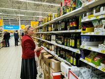 Moscow, Russia - April 14. 2018. buyer chooses olive oil in the Auchan store stock photos