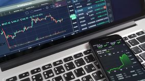 Digital currency charts on iPhone and Macbook displays