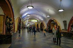 MOSCOW, RUSSIA- APRIL, 29, 2018: Indoor view of unidentified people walking close to the bronze sculpture in Ploshchad. Revolyutsii subway station in Moscow Stock Image