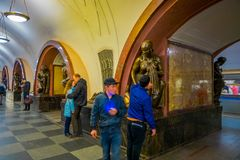 MOSCOW, RUSSIA- APRIL, 29, 2018: Indoor view of unidentified people walking close to the bronze sculpture in Ploshchad. Revolyutsii subway station in Moscow Stock Photography