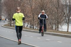 Moscow. Russia. April 9, 2019. A man on a bicycle goes to meet a man who commits a run. Sports leisure in Moscow stock images
