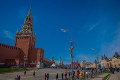 MOSCOW, RUSSIA- APRIL, 24, 2018: Outdoor view of unidentified people walking close to Kremlin chiming clock of the. Spasskaya Tower. Moscow Russia stock image